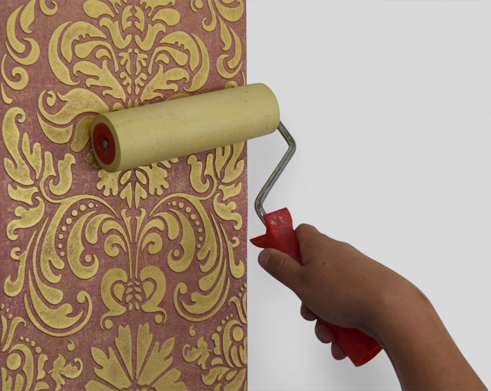3. Carefully push any bubbles, wrinkles and adhesive excess out toward the borders with a paint-roller.