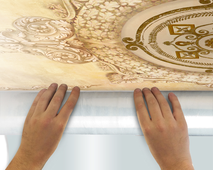 5. Unroll around 50 cm of fresco's canvas taking off a polyethylene film and hang it to the ceiling. Hold a tube with a fresco as close as possible to the ceiling.